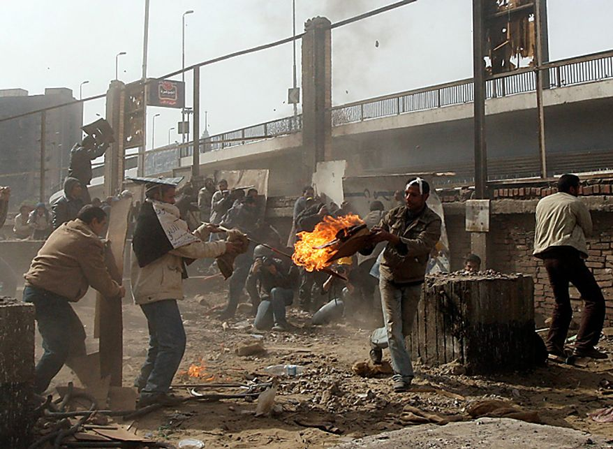 Egyptian anti-government protesters throw stones and firebombs during clashes in downtown Cairo Thursday, Feb. 3, 2011. (AP Photo/Khalil Hamra)