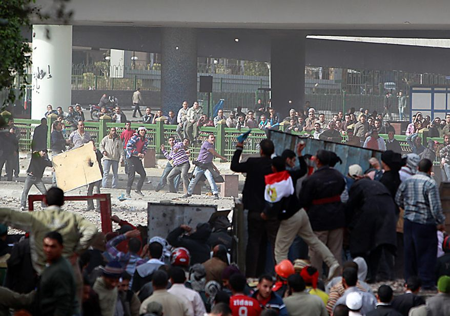 Anti-government protesters, right, clash with pro-government supporters near Cairo's main square Thursday, Feb. 3, 2011. (AP Photo/Ben Curtis)