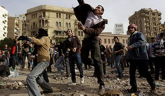 Anti-government protesters throw stones during clashes in Cairo Thursday, Feb. 3, 2011. (AP Photo/Ben Curtis)