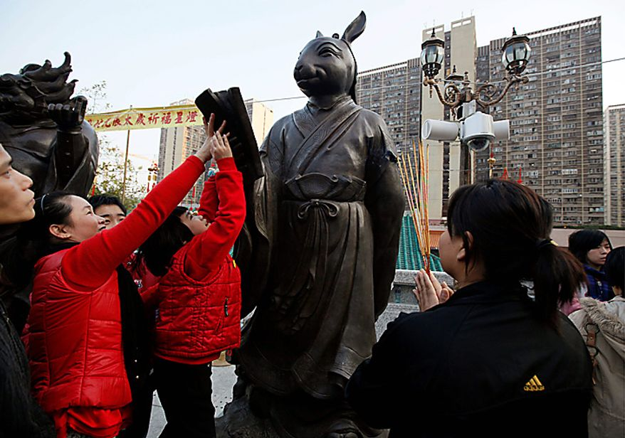 A worshipper touches a statue of a rabbit during the China's Lunar New Year at the Wong Tai Sin Temple in Hong Kong Thursday, Feb. 3, 2011. According to the Chinese zodiac, 2011 is the Year of the Rabbit. (AP Photo/Kin Cheung)