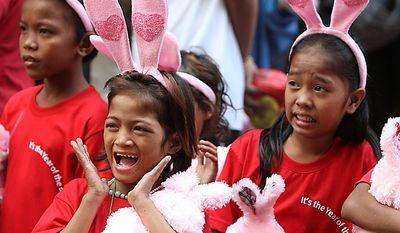 Children, wearing rabbit headbands, react to a performance during festivities at Manila's Chinatown district of Binondo to celebrate the Chinese Lunar New Year in the Philippines Thursday Feb.3, 2011, the year of the rabbit in the Chinese calendar. (AP Photo/Bullit Marquez)