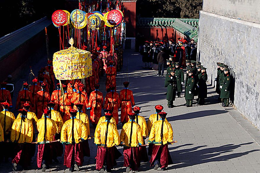 Chinese paramilitary police watch performers taking part in a re-enactment of a customary ceremony where the emperor prays for a good harvest during the lunar new year at the Temple of Heaven in Beijing Thursday, Feb. 3, 2011. (AP Photo/Ng Han Guan)