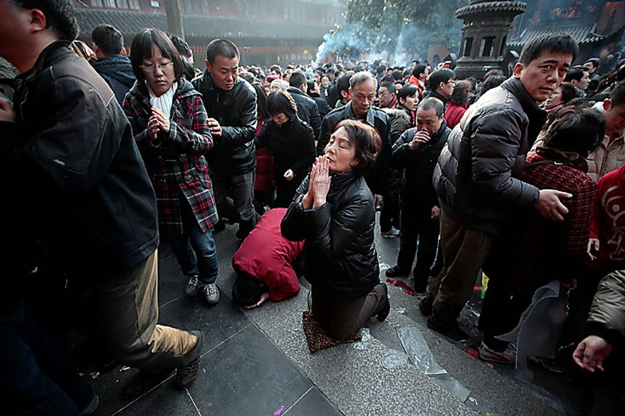 Worshippers offer the first prayer of the new year at a temple Thursday, Feb. 3, 2011, in Shanghai, China. According to the Chinese zodiac, 2011 is the Year of the Rabbit. (AP Photo/Eugene Hoshiko)