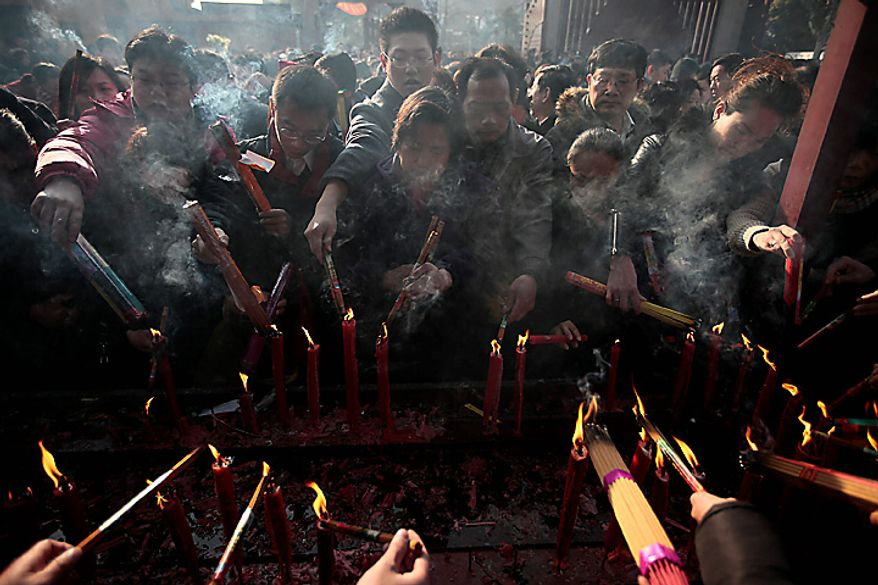 Worshippers light their joss sticks to offer the first prayer of the lunar new year at a temple Thursday, Feb. 3, 2011, in Shanghai, China. According to the Chinese Zodiac, 2011 is the Year of the Rabbit. (AP Photo/Eugene Hoshiko)