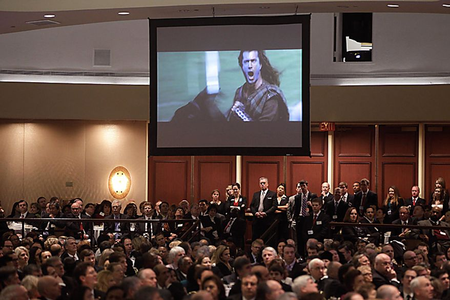 """The audience watches as screenwriter Randall Wallace (not pictured) shows a clip from the movie """"Braveheart,"""" starring Mel Gibson, before Mr. Wallace spoke at the National Prayer Breakfast in Washington on Thursday, Feb. 3, 2011. (AP Photo/Charles Dharapak)"""