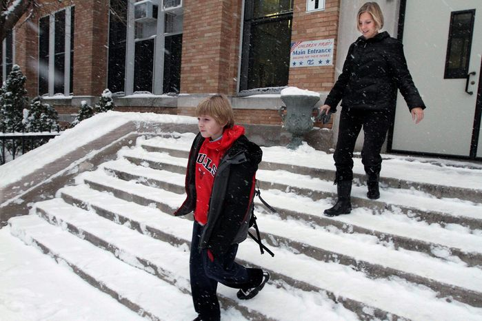 "ASSOCIATED PRESS PHOTOGRAPHS Erik Yehl, 11, leaves school with his mother, Kirsten. Like King George VI, whose battle to overcome stuttering is depicted in ""The King's Speech,"" Erik struggles with the speech impediment. The movie's powerful message for him is, ""I'm not stupid."""