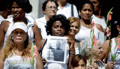 "ASSOCIATED PRESS Surrounded by activists, Rosario Morales de la Rosa, a member of the Cuban dissident group Ladies in White, holds up a picture of her son, a political prisioner, as they demonstrate Sunday during their weekly march in Havana. The sign reads in Spanish ""Freedom now!"""