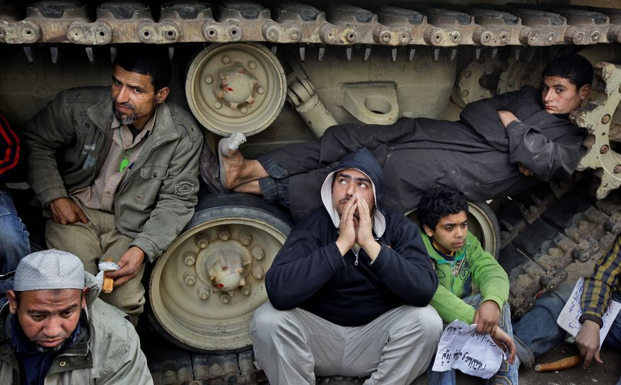 Anti-government protesters squat on the tracks of Egyptian army tanks Sunday to prevent them from moving near Tahrir Square in Cairo. (Associated Press)