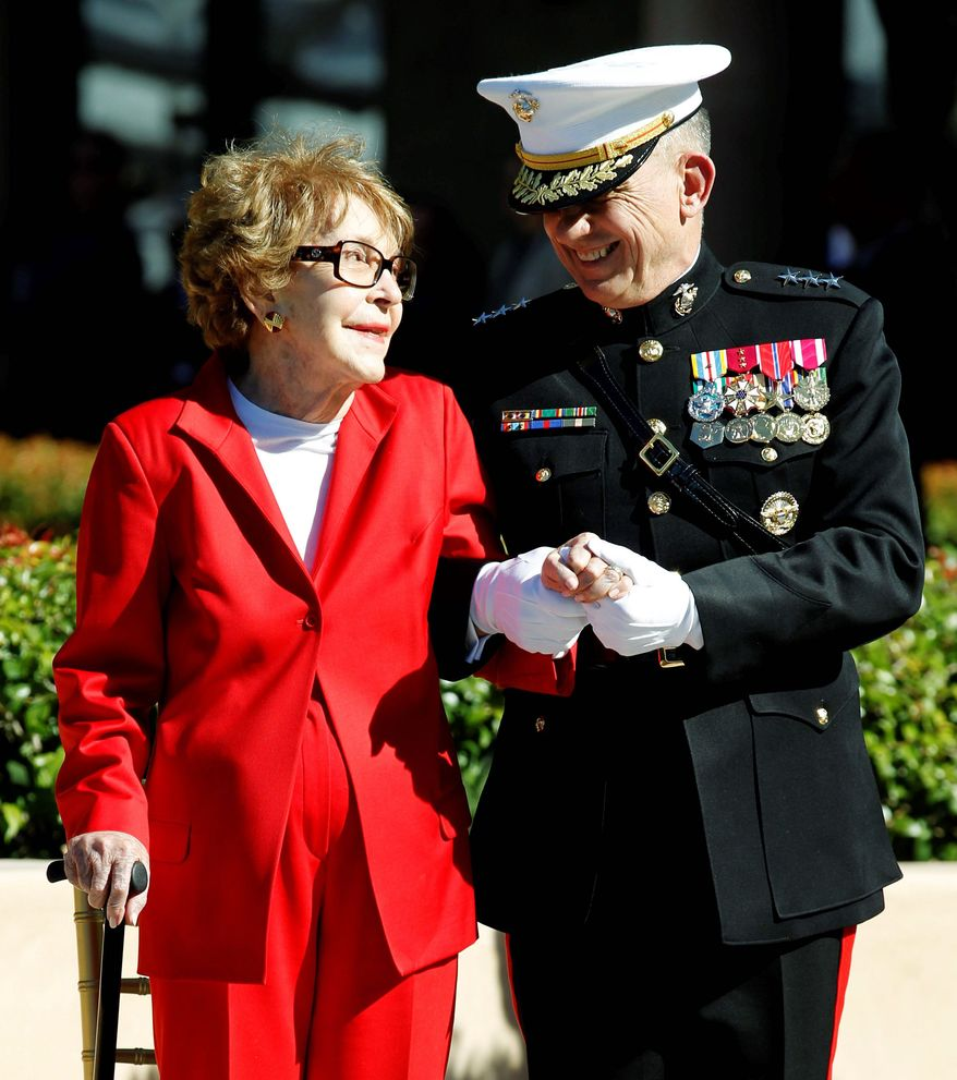 Former first lady Nancy Reagan is assisted by Marine Lt. Gen. George J. Flynn at a wreath-laying ceremony for former President Ronald Reagan during his centennial birthday celebration in Simi Valley, Calif., in 2011. (Associated Press) ** FILE **