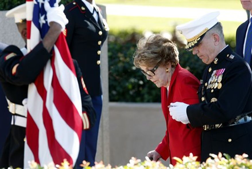 Former first lady Nancy Reagan is helped by U.S. Marine Lt. Gen. George J. Flynn as she arrives for a wreath laying ceremony at the memorial of her husband, former U.S. President Ronald Reagan during the centennial birthday celebration at at the Ronald Reagan Presidential Library, in Simi Valley, Calif, on Sunday Feb. 6, 2011. (AP Photo/Richard Vogel)