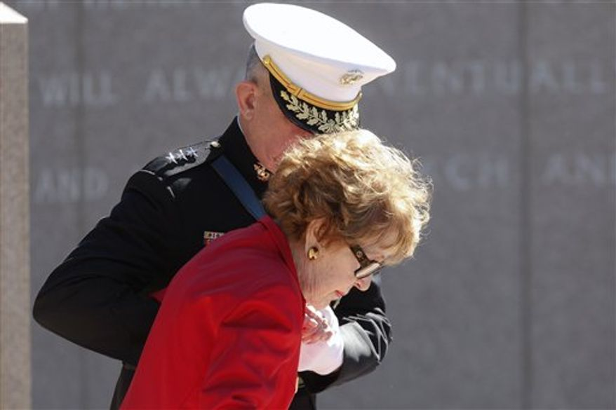 Former first lady Nancy Reagan is helped by U.S. Marine Lt. Gen. George J. Flynn as she arrives for a wreath laying ceremony at the memorial of her husband, former U.S. President Ronald Reagan during the centennial birthday celebration at the Ronald Reagan Presidential Library, in Simi Valley, Calif, on Sunday Feb. 6, 2011. (AP Photo/Richard Vogel)
