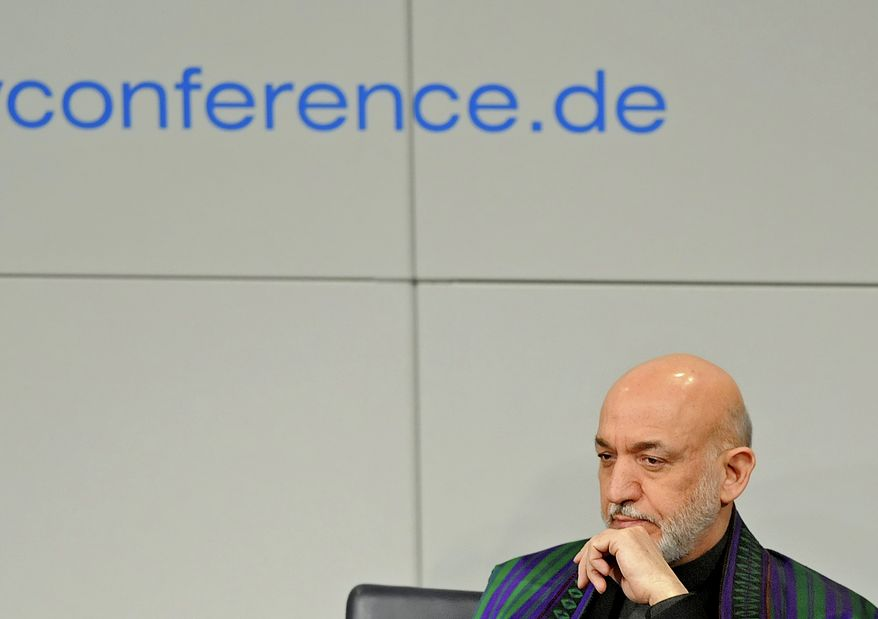 Afghan President Hamid Karzai is seated at the podium during the International Conference on Security Policy in Munich on Sunday, Feb. 6, 2011. (AP Photo/Jens Meyer)