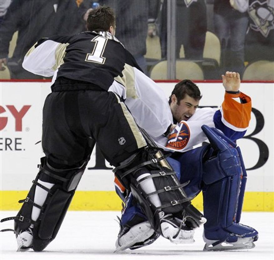 Pittsburgh Penguins' Eric Tangradi, right, collides with New York Islanders goalie Rick DiPietro (39) behind the net during the first period of an NHL hockey game in Pittsburgh, Wednesday, Feb. 2, 2011. (AP Photo/Gene J. Puskar)
