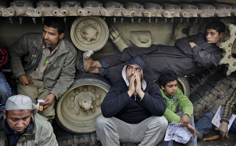 Anti-government protesters sit on and lie inside the tracks of an Egyptian army tank, both to prevent the tank from moving and to shield themselves from the rain, at a protest site opposite the Egyptian Museum near Tahrir Square in downtown Cairo on Sunday, Feb. 6, 2011. (AP Photo/Ben Curtis)