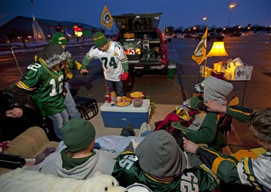 Wearing his #74 jersey Green Bay Packers fan Troy Knaus leads a group of family and friends in a prayer Sunday, Feb. 6, 2011, in the Lambeau Field parking lot in Green Bay, Wis. prior to the Super Bowl.   The Packers will face the Pittsburgh Steelers in the NFL football Super Bowl XLV in Arlington, Texas. (AP Photo/Mike Roemer)