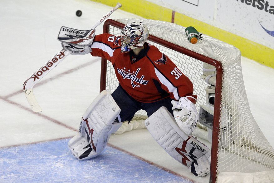 Washington Capitals goalie Michal Neuvirth (30), of the Czech Republic, deflects a shot from the Pittsburgh Penguins in the first period of an NHL hockey game in Washington, on Sunday, Feb. 6, 2011. (AP Photo/Jacquelyn Martin)