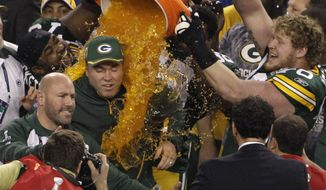 Green Bay Packers head coach Mike McCarthy, center, is dunked by T.J. Lang, right, and other teammates following their 31-25 win in the NFL Super Bowl XLV football game against the Pittsburgh Steelers Sunday, Feb. 6, 2011, in Arlington, Texas. (AP Photo/Lynne Sladky)