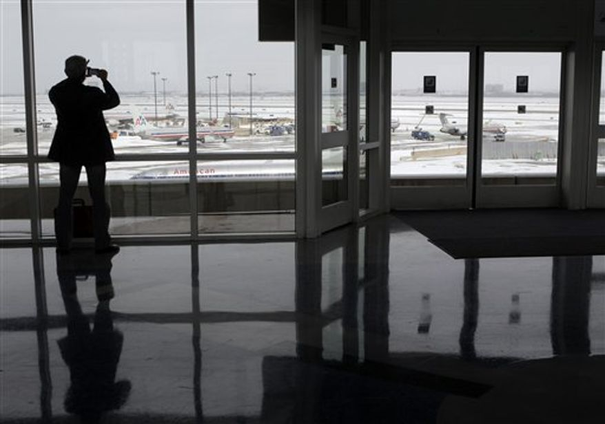 Ron Zirkle, whose flight to Memphis, Tenn., has been canceled due to winter storms, is silhouetted against a snow-covered tarmac, Friday, Feb. 4, 2011, at Dallas-Fort Worth International Airport in Grapevine, Texas, Friday, Feb. 4, 2011. Another blast of winter weather slammed Dallas with up to 5 inches of snow, making driving hazardous and forcing the cancellation of hundreds of flights as tens of thousands of football fans descended on North Texas for the NFL's Super Bowl football game with the Green Bay Packers and the Pittsburgh Steelers at Cowboys Stadium, Sunday, Feb. 6 in Arlington, Texas. (AP Photo/Jae C. Hong)