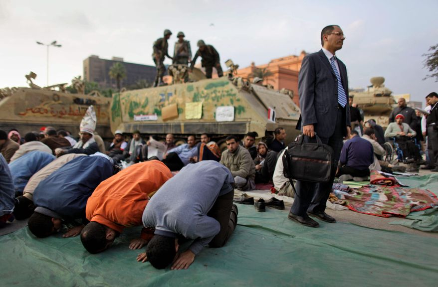 Anti-government protesters pray in front of an army armored vehicle as one stands to have his picture taken by a friend at the continuing protest in Tahrir Square in downtown Cairo. Egypt's embattled regime announced a 15 percent raise for government employees in an effort to defuse popular anger. (Associated Press)