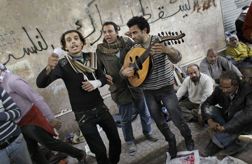 Musicians, one (center right) playing the oud, entertain anti-government protesters with songs against Egyptian President Hosni Mubarak at the continuing demonstration in Tahrir Square in central Cairo on Friday, Feb. 4, 2011. (AP Photo/Ben Curtis)