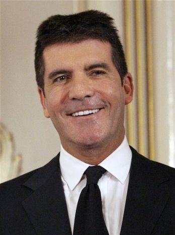 FILE- In this June 6, 2010 file photo, British music mogul Simon Cowell holds his honorary Bafta Award, during the British Academy Television Awards at the London Palladium in central London. (AP Photo/Joel Ryan, file)