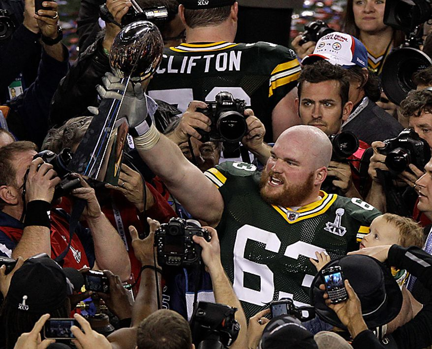 The Green Bay Packers' Scott Wells celebrates with the Lombardi Trophy following their NFL Super Bowl XLV win against the Pittsburgh Steelers on Sunday, Feb. 6, 2011, in Arlington, Texas. The Packers won 31-25. (AP Photo/Charlie Riedel)
