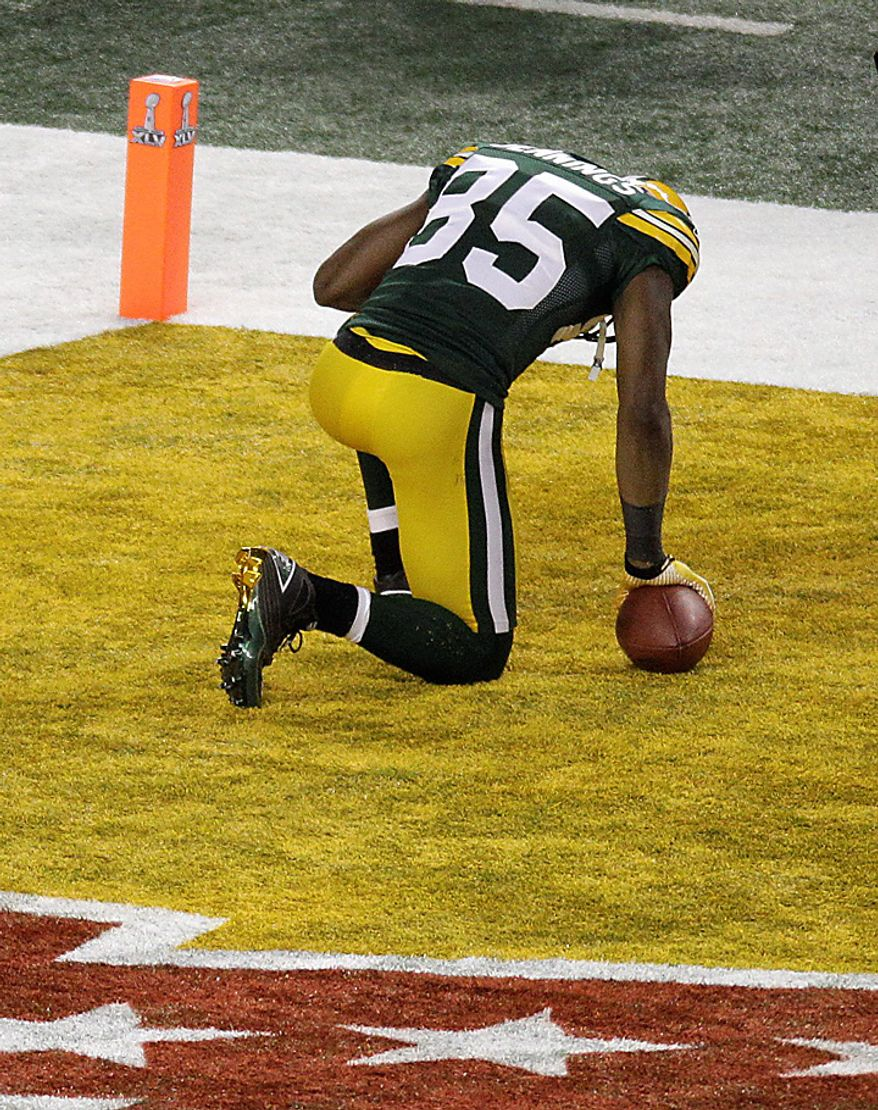 The Green Bay Packers' Greg Jennings kneels in the end zone after making a touchdown reception against the Pittsburgh Steelers during the first half of the NFL Super Bowl XLV football game on Sunday, Feb. 6, 2011, in Arlington, Texas. (AP Photo/Charlie Riedel)