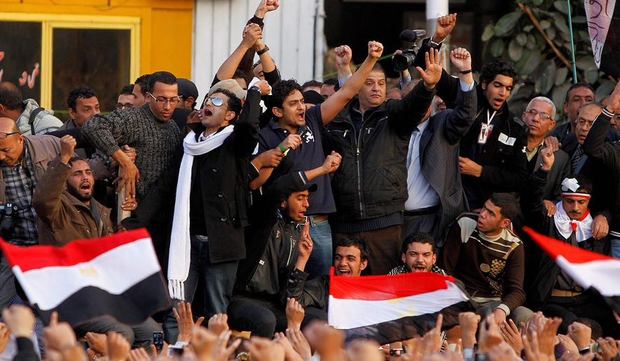 """Egyptian Wael Ghonim (center), a Google Inc. marketing manager who was a key organizer of the online campaign that sparked the first protest on Jan. 25, talks to the crowd at Tahrir Square in Cairo on Tuesday. Another young protester drew applause when he declared: """"We will not abandon our demand and that is the departure of the regime."""" (Associated Press)"""
