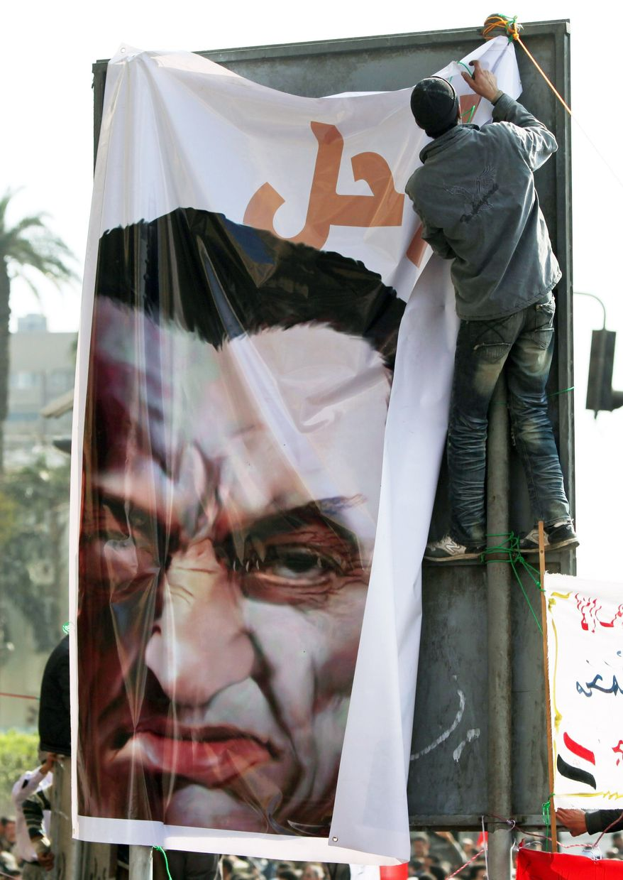MUGGED: A protester puts up a caricature of Egyptian President Hosni Mubarak in Cairo as thousands continue to call for his ouster. (Associated Press)