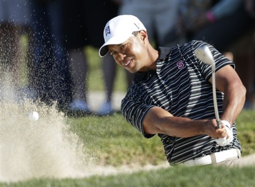 FILE- In this file photo dated Saturday, Jan. 29, 2011. Tiger Woods blast from a bunker during the Farmers Insurance Open golf tournament in San Diego, U.S.A.,.  It is announced Monday Feb. 7, 2011,  that American army officer Lt. Col. Michael Rowells, serving in war-torn Afghanistan has won the chance to play golf with Tiger Woods in the Dubai Desert Classic pro-am on Wednesday Feb. 9. Rowells has a nine handicap and is currently deployed with the 401st Army Field Support Brigade in Afghanistan, and will fly out to Dubai specially for the Pro-Am tournament and his big chance to play with Woods. (AP Photo/Gregory Bull, file)