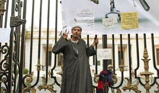 An anti-government protester gestures outside the Egyptian parliament in Cairo on Wednesday. About 2,000 protesters waved huge flags outside the parliament. They chanted slogans demanding the dissolving of the legislature, where almost all the seats are held by President Hosni Mubarak's ruling party. (Associated Press)