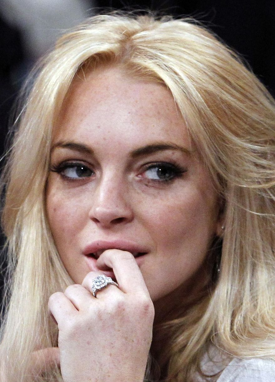 ** FILE ** In this Jan. 9, 2011, file photo, Lindsay Lohan attends the Los Angeles Lakers New York Knicks NBA basketball game in Los Angeles. Prosecutors say they plan to charge Lohan on Wednesday, Feb. 9, 2011, with felony grand theft of a $2,500 necklace reported stolen from a jewelry store. (AP Photo/Alex Gallardo, File)