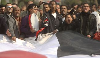 Protesters carry a giant Egyptian flag in front of the country's parliament in Cairo on Wednesday in the anti-Mubarak movement's first expansion outside Tahrir Square. The demonstrators chanted slogans demanding the dissolution of the legislative body, which is controlled almost entirely by the ruling party. (Associated Press)
