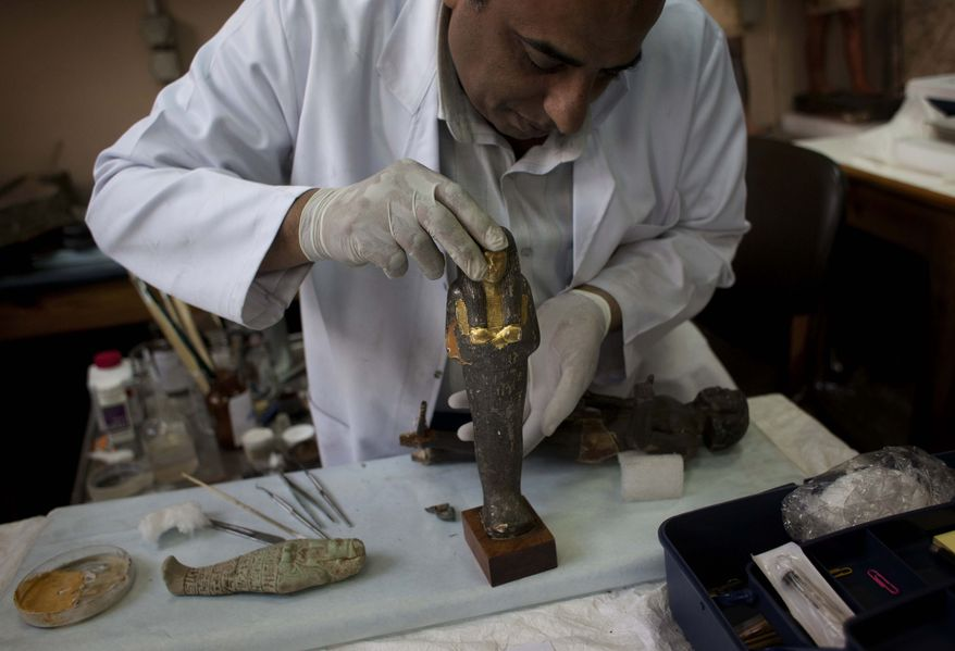 An Egyptian restorer fixes one the pieces that was broken by looters at the Egyptian Museum in Cairo, Egypt, on Thursday, Feb. 10, 2011. Would-be looters broke into Cairo's famed Egyptian Museum on Saturday, Jan. 29, ripping the heads off two mummies and damaging about 75 small artifacts before being caught and detained by army soldiers. (AP Photo/Emilio Morenatti)