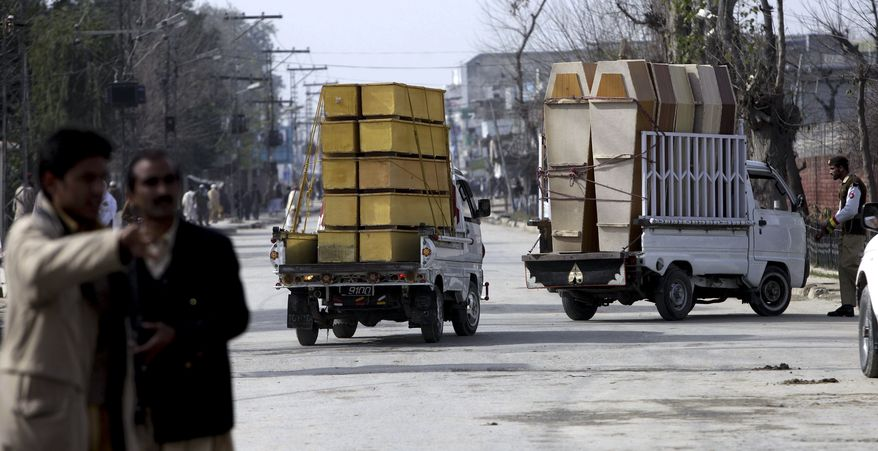 Vehicles carrying coffins head to the Pakistan army training camp in Mardan near Peshawar, Pakistan, on Thursday, Feb. 10, 2011. A suicide bomber attacked soldiers during morning exercises at a Pakistani army training camp killing 31 troops and injuring dozens others, police and the military said. (AP Photo/Mohammad Sajjad)