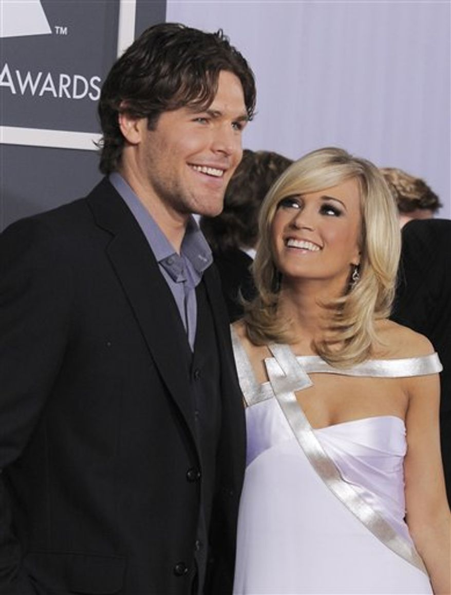 FILE - Carrie Underwood and Ottawa Senators hockey player Mike Fisher arrive at the Grammy Awards in this Jan. 31, 2010 file photo taken in Los Angeles. The Senators are sending Fisher to the Nashville Predators for a first-round draft pick and a conditional pick. Fisher, who is married to country music star Carrie Underwood, has 24 points this season. (AP Photo/Chris Pizzello, File)