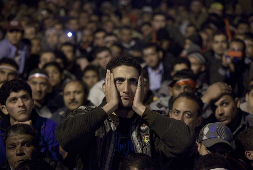 Anti-government protesters watch on a big screen as Egyptian President Hosni Mubarak makes a televised statement to his nation in Tahrir Square in downtown Cairo, Egypt, on Thursday, Feb. 10, 2011. (AP Photo/Emilio Morenatti)