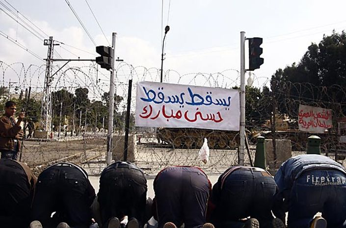Egyptian protesters pray as the army blocked the entrence to Ettehadyya Presidential Palace in Cairo by barbed wire Friday, Feb. 11, 2011. The Egyptian government announced later Friday that President Hosni Mubarak has resigned. (AP Photo)