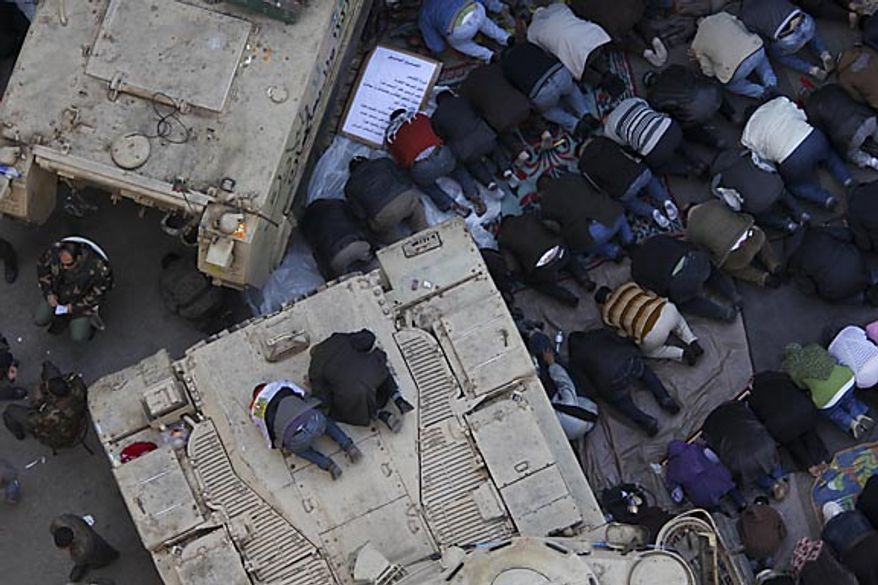 Anti-government protesters pray atop an Egyptian army vehicle in Tahrir Square in downtown Cairo Friday, Feb. 11, 2011. The Egyptian government announced later Friday that President Hosni Mubarak has stepped down. (AP Photo/Tara Todras-Whitehill)