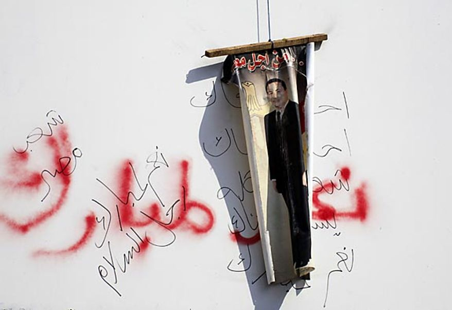 A poster showing Egyptian President Hosni Mubarak is hung by anti-government protesters Friday, Feb. 11, 2011, over pro-Mubarak slogans set by his supporters a week ago in a Cairo street. Egypt's government announced later Friday that Mr. Mubarak has stepped down. (AP Photo/Amr Nabil)