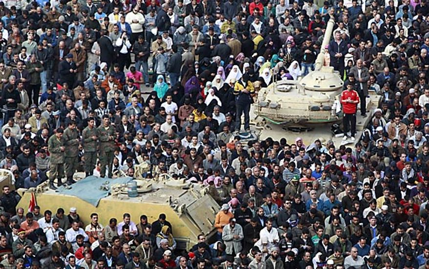 Anti-government protesters as well as Egyptian army soldiers on top of their vehicles, participate in traditional Muslim Friday prayers in Tahrir Square in downtown Cairo Friday, Feb. 11, 2011. The government announced later Friday that President Hosni Mubarak has stepped down. (AP Photo/Ben Curtis)