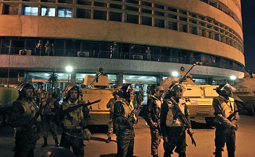 Army soldiers stand guard as anti-government protesters surround the state television building following Egyptian President Hosni Mubarak's televised speech, on the Corniche in downtown Cairo Thursday, Feb. 10, 2011. In that speech, Mr. Mubarak refused to quit, but the government announced Friday that he has stepped down. (AP Photo/Mohammed Abu Zaid)