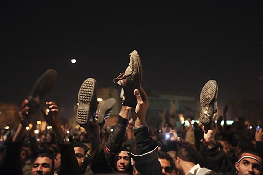 Anti-government protesters in Cairo's Tahrir Square hold their shoes up in reaction to Egyptian President Hosni Mubarak's televised statement to his nation Thursday, Feb. 10, 2011. Mr. Mubarak refused to resign in that speech, but the government announced Friday that he has stepped down. (AP Photo/Tara Todras-Whitehill)