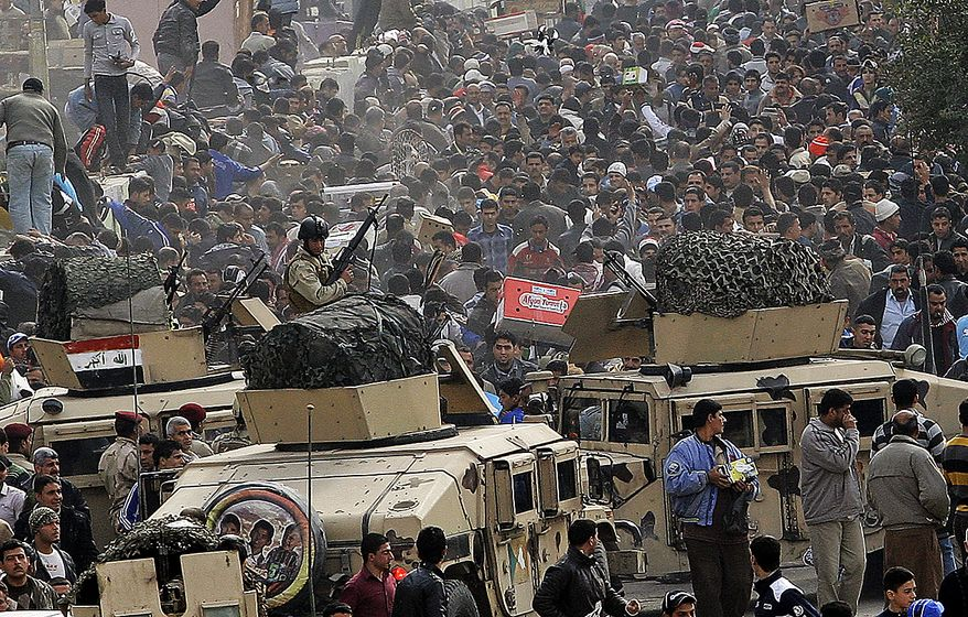 Iraqi army soldiers stand guard while protesters chant anti-government slogans during a demonstration in Baghdad, Iraq, on Friday, Feb. 11, 2011. (AP Photo/Hadi Mizban)