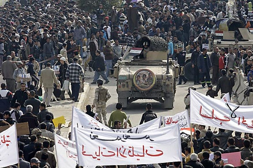"""Iraqi army soldiers stand guard while protesters chant anti-government slogans during a demonstration in Baghdad, Iraq, Friday, Feb. 11, 2011.  In at least four morning demonstrations across Baghdad, protesters painted a picture of their homeland that they said has fewer services and more corruption than in Egypt. The banners in Arabic read, """"From Cairo to Baghdad, no for corruption"""" and """"Maliki, like Saddam he do not care about orphans."""" (AP Photo/Hadi Mizban)"""
