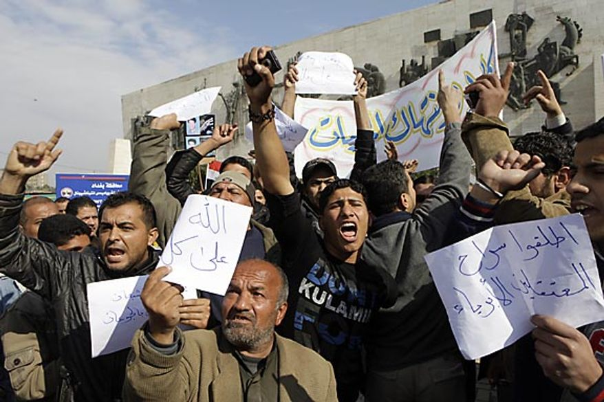 "Protesters chant anti-government slogans during a demonstration in Baghdad, Iraq, Friday, Feb. 11, 2011. In at least four morning demonstrations across Baghdad, protesters painted a picture of their homeland that they said has fewer services and more corruption than in Egypt. The banners in Arabic read, ""From Cairo to Baghdad, no for corruption"" and ""Maliki, like Saddam he does not care about orphans."" (AP Photo/Khalid Mohammed)"