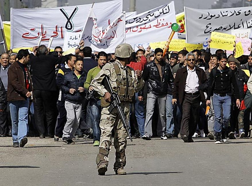 """An Iraqi army soldier stands guard while protesters chant anti-government slogans during a demonstration in Baghdad, Iraq, Friday, Feb. 11, 2011. In at least four morning demonstrations across Baghdad, protesters painted a picture of their homeland that they said has fewer services and more corruption than in Egypt. The banners in Arabic read, """"From Cairo to Baghdad, no for corruption"""" and """"Maliki, like Saddam he does not care about orphans."""" (AP Photo/Hadi Mizban)"""