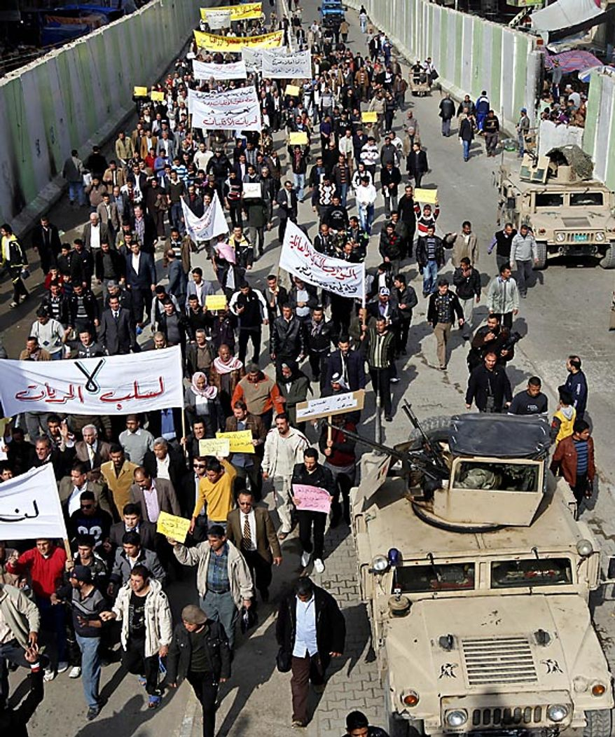 "Protesters chant anti-government slogans during a demonstration in Baghdad, Iraq, Friday, Feb. 11, 2011. In at least four morning demonstrations across Baghdad, protesters painted a picture of their homeland that they said has fewer services and more corruption than in Egypt. The banners in Arabic read, ""From Cairo to Baghdad, no for corruption"" and ""Maliki, like Saddam he does not care about orphans."" (AP Photo/Hadi Mizban)"