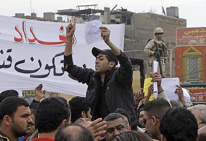 """Protesters chant anti-government slogans during a demonstration in Baghdad, Iraq, Friday, Feb. 11, 2011. In at least four morning demonstrations across Baghdad, protesters painted a picture of their homeland that they said has fewer services and more corruption than in Egypt. The banners in Arabic read, """"From Cairo to Baghdad, no for corruption"""" and """"Maliki, like Saddam he do not care about orphans."""" (AP Photo/Khalid Mohammed)"""