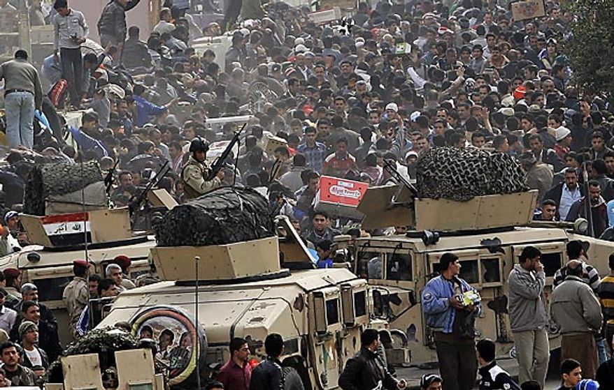 Iraqi army soldiers stand guard while protesters chant anti-government slogans during a demonstration in Baghdad, Iraq, Friday, Feb. 11, 2011. In at least four morning demonstrations across Baghdad, protesters painted a picture of their homeland that they said has fewer services and more corruption than in Egypt. (AP Photo/Hadi Mizban)